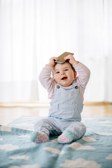 Portrait of baby girl sitting on blanket holding smartphone on the head - BRF001304