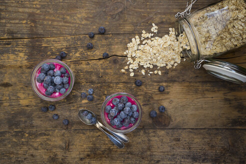 Two glasses of overnight oats with blueberries and berry juice on wood - LVF004737
