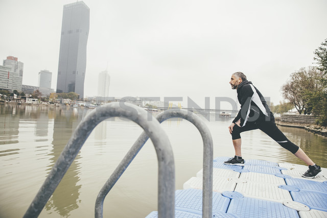 Austria, Vienna, jogger doing stretching exercise on Danube Island - AIF000312 - AustrianImages/Westend61