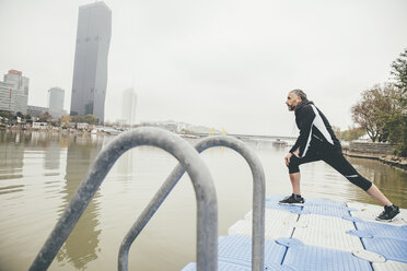 Austria, Vienna, jogger doing stretching exercise on Danube Island - AIF000312