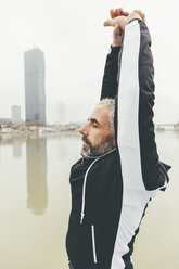 Austria, Vienna, jogger doing stretching exercise on Danube Island - AIF000315