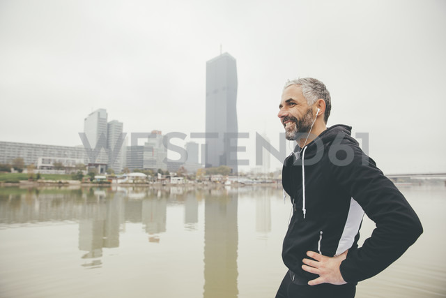 Austria, Vienna, portrait of smiling jogger with earphones in front of Donau City - AIF000318 - AustrianImages/Westend61