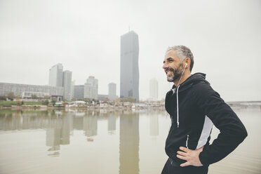 Austria, Vienna, portrait of smiling jogger with earphones in front of Donau City - AIF000318