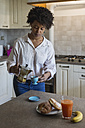 Young woman pouring espresso into cup in her kitchen - MAUF000420