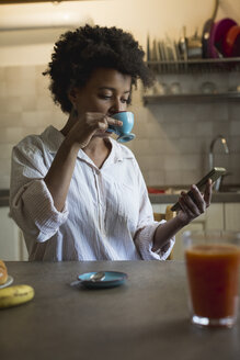 Portrait of young woman drinking espresso in her kitchen while looking at phablet - MAUF000423