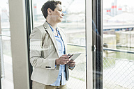 Businesswoman with digital tablet at the window - UUF006777