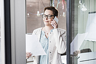 Businesswoman on cell phone reading document - UUF006807