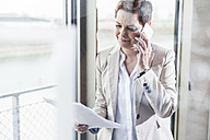 Businesswoman on cell phone reading document - UUF006813