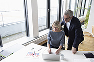 Businessman and woman working together in office using laptop - RBF004276