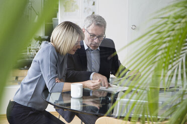 Businessman and woman working together in office discussing documents - RBF004279