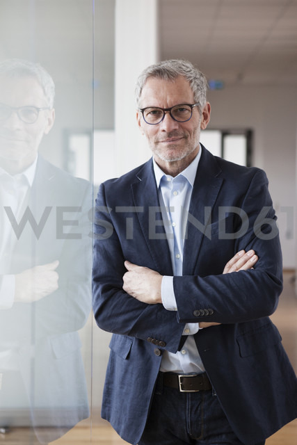 Successful businessman standing in his office with arms crossed - RBF004321