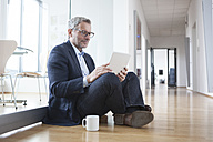 Successful businessman sitting on floor, using digital tablet in his office - RBF004327