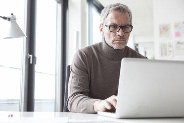 Mature man sitting in office using laptop - RBF004333