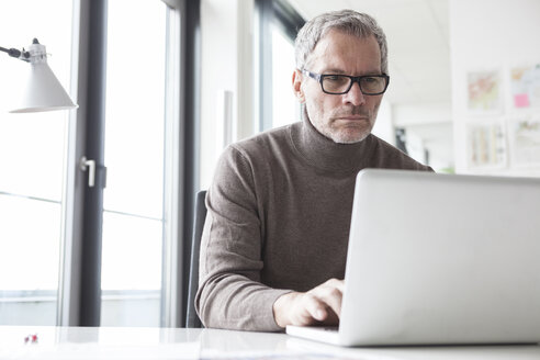 Mature man sitting in office using laptop - RBF004333