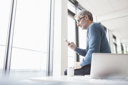 Mature man sitting in office with laptop, using smart phone - RBF004345