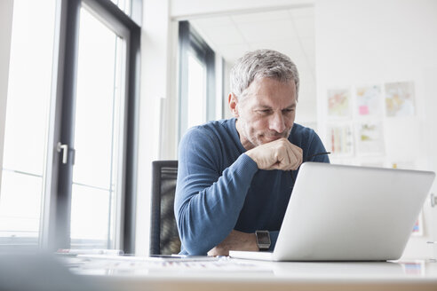 Mature man sitting in office using laptop - RBF004348