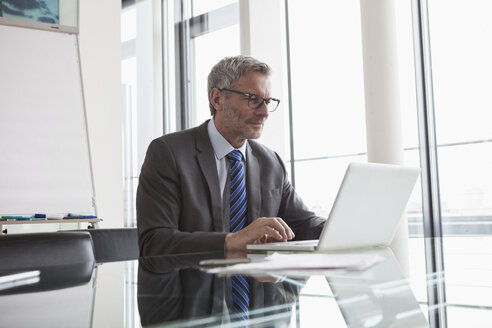 Mature manager sitting in office using laptop - RBF004354