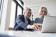 Businessman and woman working together in office using laptop - RBF004378