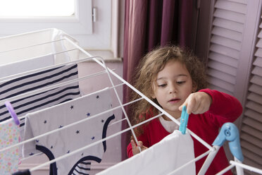Little girl hanging out the laundry on a drying rack - LITF000259