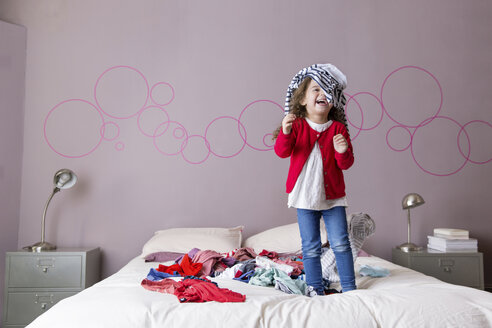 Laughing little girl playing on parents' bed with laundry - LITF000265