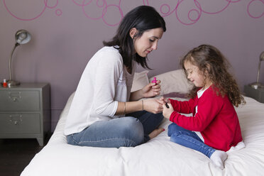 Mother and little daughter sitting together on the bed applying nail varnish - LITF000268
