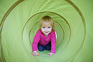 Portrait of smiling little girl crawling in a bright green tunnel - LHF000497