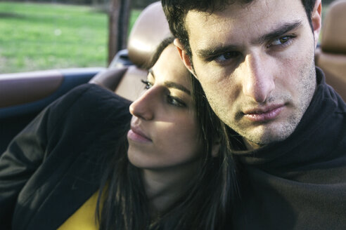 Portrait of young man sitting with his girlfriend in a convertible - ABZF000332
