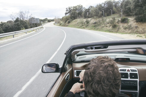 Man driving a convertible car on empty country road - ABZF000335