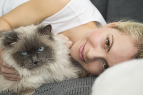 Portrait of smiling young woman lying on couch with her cat - LFOF000205