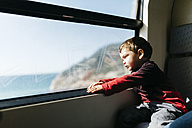 Little boy on his first train ride looking through the window - JRFF000538