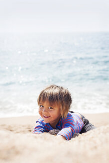 Portrait of little boy playing on the beach at seafront - VABF000436
