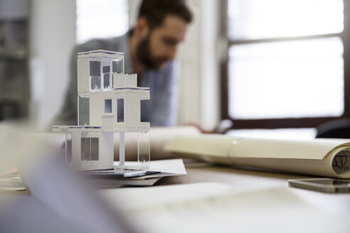 Desktop with architectural model and man in background - FKF001772