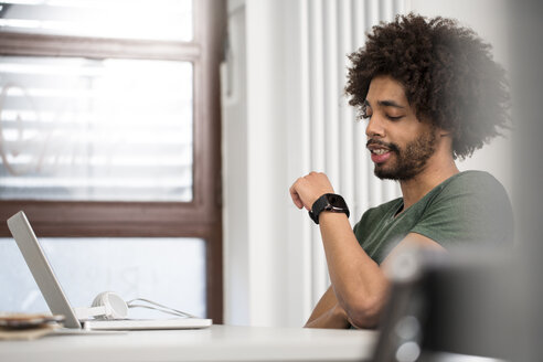 Creative professional in office looking at smartwatch - FKF001778