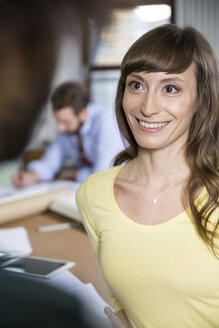 Smiling young woman office looking at colleague - FKF001790