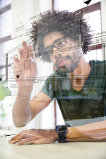 Young man using transparent touchscreen display - FKF001817