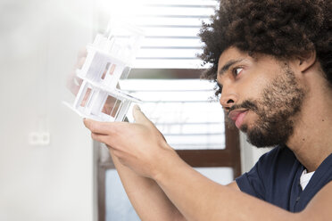 Young man examining architectural model - FKF001823