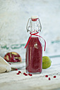 Glass bottle of pomegranate smoothie - ASF005883