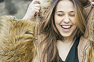 Portrait of laughing woman putting  hood of a fur jacket on - ABZF000336