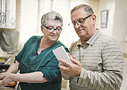 Senior couple looking at smartphone at home - EPF000068