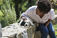 Young woman stroking her dog on a stone wall - MAUF000441