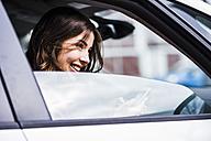 Brunette woman sitting in car looking through window - UUF006855