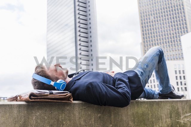 Young businessman lying on wall listening music with headphones - UUF006885
