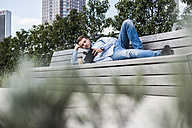 Young man lying on bench drinking coffee - UUF006915