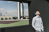 Young man wearing headphones leaning on wall with eyes closed - UUF006921