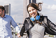 Happy young couple , woman jumping with headphones aroung neck - UUF006924