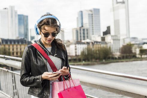 Young woman walking in the city wearing headphones - UUF006930