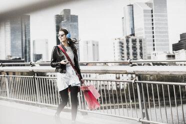 Young woman walking in the city wearing headphones - UUF006933