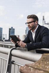Young businessman using digital tablet standing on bridge - UUF006942