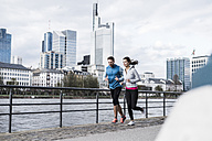 young couple running at the river - UUF006954