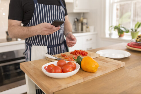 Man using smartphone while preparing food in the kitchen, partial view - BOYF000255